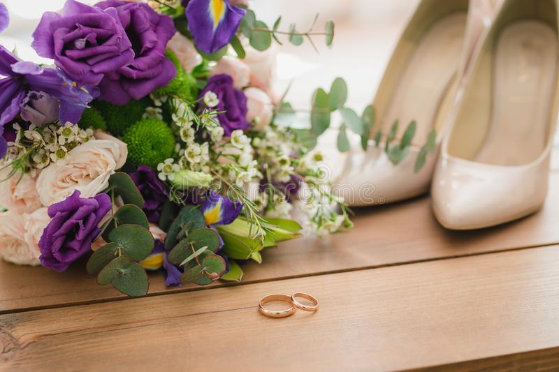 On a wooden table a wedding bouquet with green leaves, purple and white flowers, wedding rings royalty free stock images