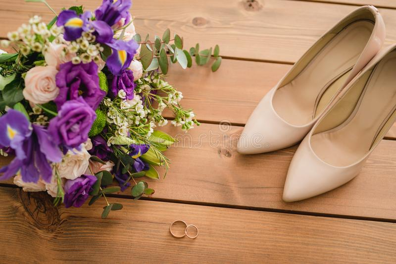 On a wooden table a wedding bouquet with green leaves, purple and white flowers, wedding rings stock photography