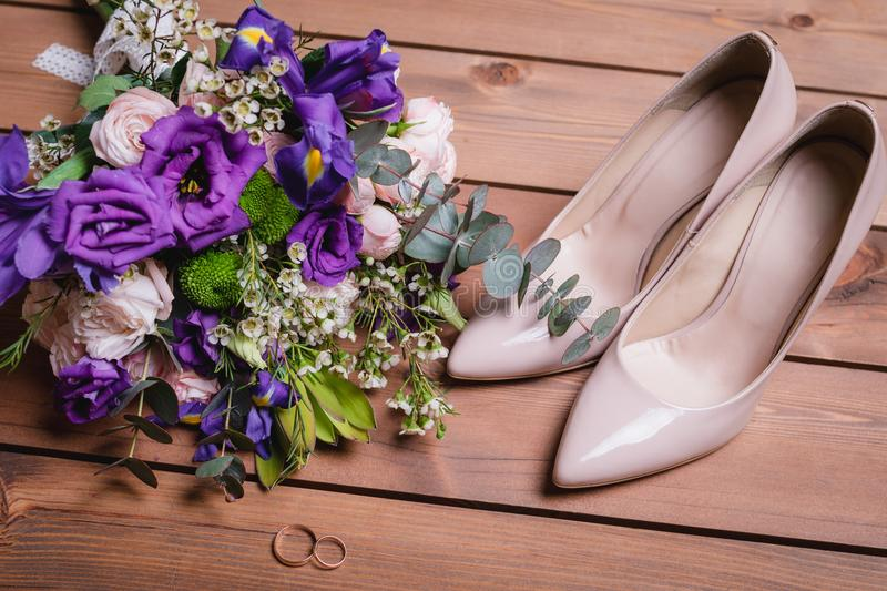 On a wooden table a wedding bouquet with green leaves, purple and white flowers, wedding rings royalty free stock photo