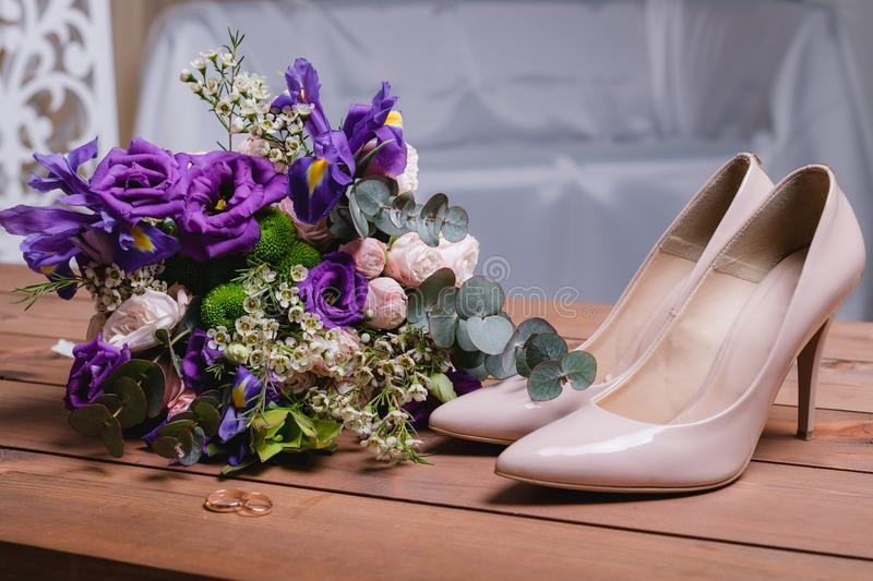 On a wooden table a wedding bouquet with green leaves, purple and white flowers, wedding rings stock photo