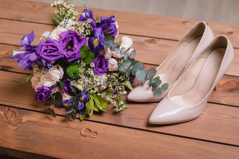 On a wooden table a wedding bouquet with green leaves, purple and white flowers, wedding rings stock image
