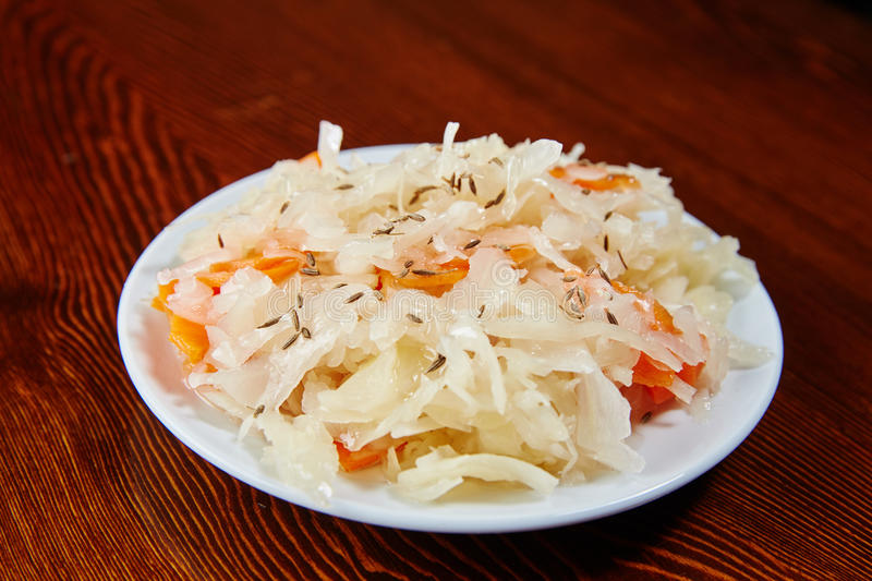 On the wooden table is a white plate with a salad of pickled cab royalty free stock photography