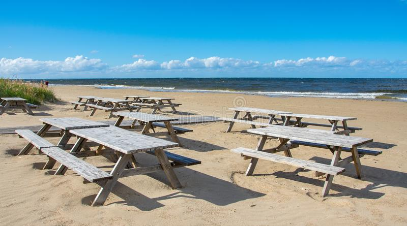 Wooden tables and benches of a summer cafe on a deserted beach in the bright sunny day of the beginning of autumn.  royalty free stock images