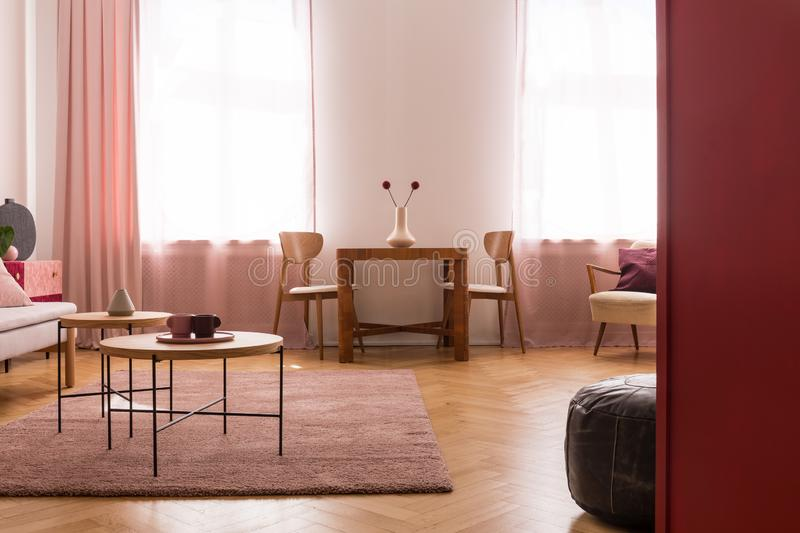 Wooden tables on purple carpet in living room interior with pink drapes at window. Real photo. Wooden tables on purple carpet in living room interior with pink stock photo