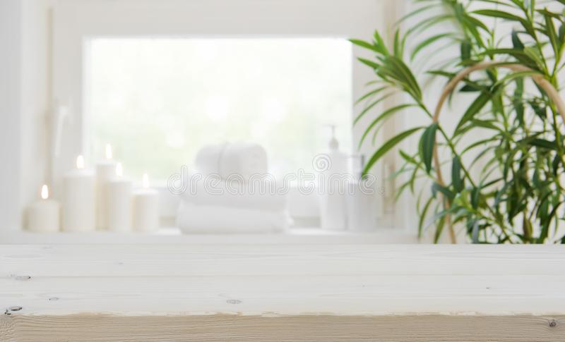 Wooden tabletop with copy space over blurred spa window background.  stock images