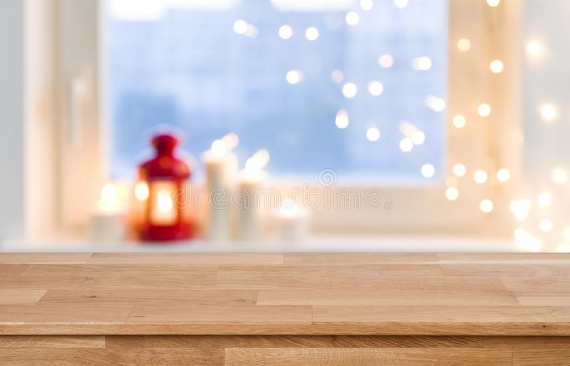 Wooden tabletop over blurred christmas lights on frosted window background.  stock photography