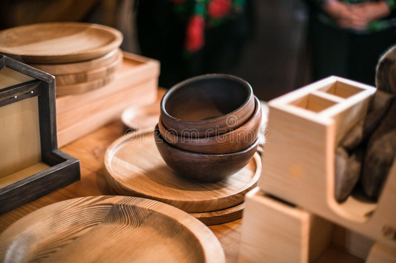 Wooden tableware in the light of the sun. Craftwork kitchenware is standing on the wooden table in a farm countryside stock images