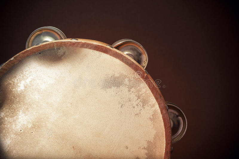 Wooden Tambourine on Brown Background. Old retro wooden tambourine on brown background, closeup view of details royalty free stock images