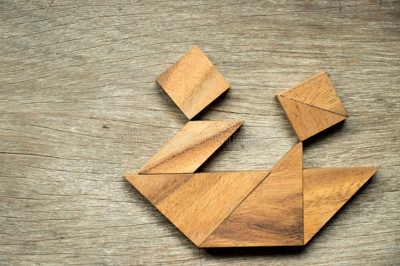 Wood tangram puzzle in couple sailing the boat shape background stock images