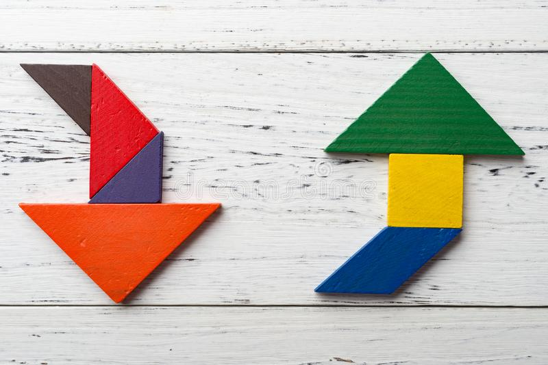 Wooden tangram in two arrow shapes one is up and the other is down. Wooden tangram in two arrow shapes one is up and the other one is down stock image