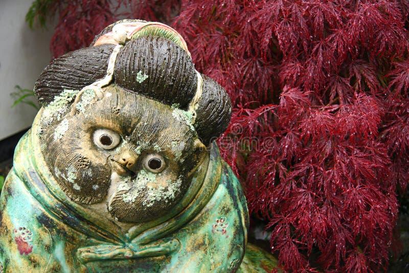 Wooden tanuki female. Head of wooden tanuki statue in japanese garden stock image