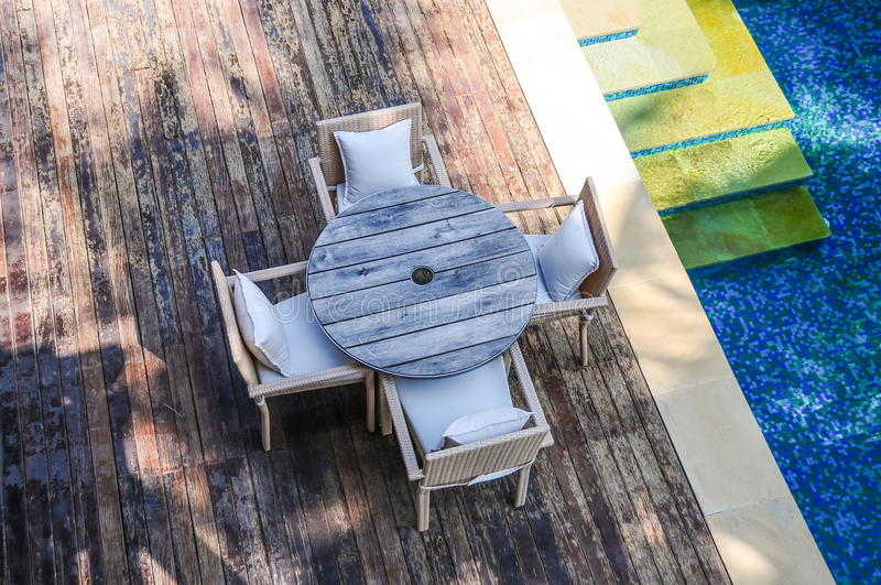 Wooden Terace of tropical resort poolside. Wooden Terace with tabele and chairs of tropical resort poolside. View from above stock photos
