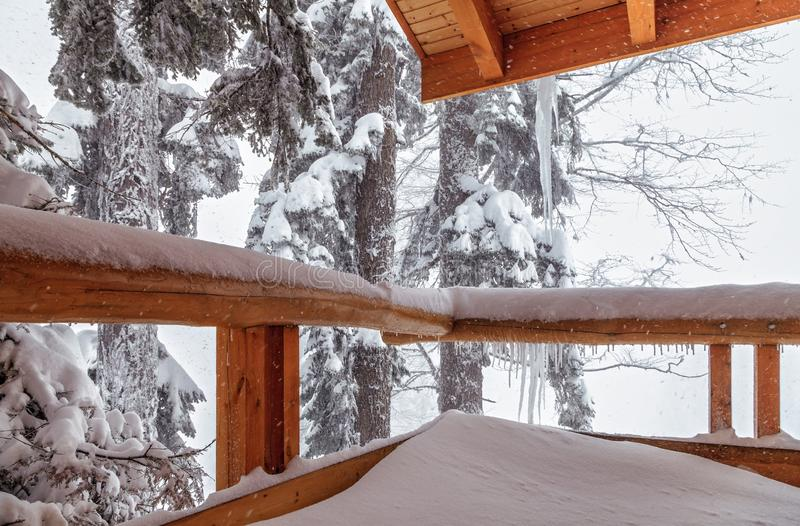Wooden terrace in mountain forest at snowy winter during hard snowstorm with fir trees on background. Scenic winter countryside. Wooden terrace in mountain royalty free stock photo