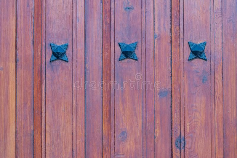Wooden texture background. Closeup of a detail from a wooden red brown entrance door with three metal stars on the wooden planks. stock photo