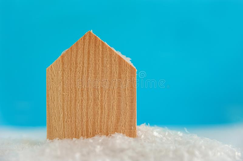 Wooden texture house on artificial snow on blue background with copy space. Christmas tree, minimal New Year s card. Holidays, Con. Gratulation concept. Place royalty free stock images