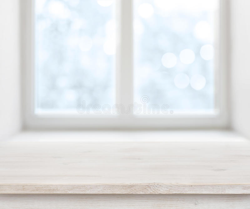 Wooden texture table surface over abstract frosty winter window background royalty free stock photo