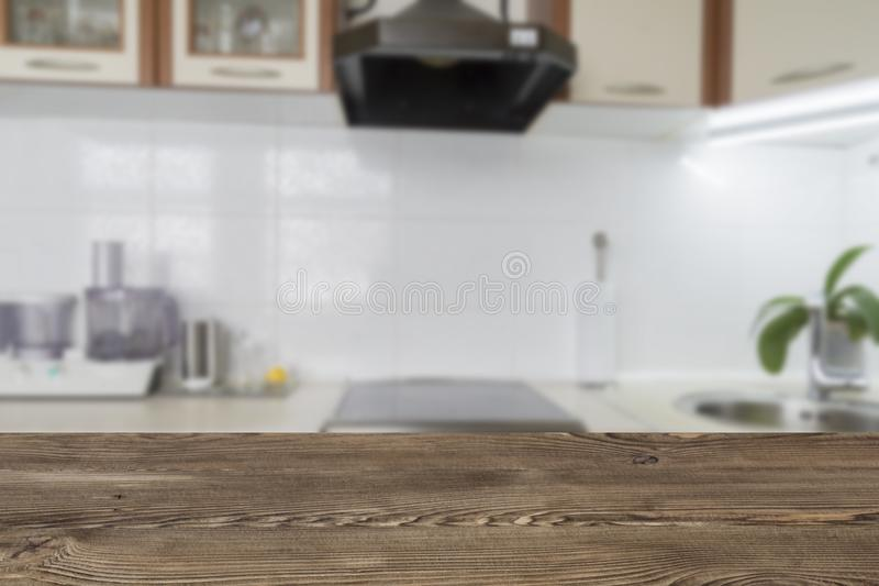 Wooden textured table over blurred kitchen interior background stock photos