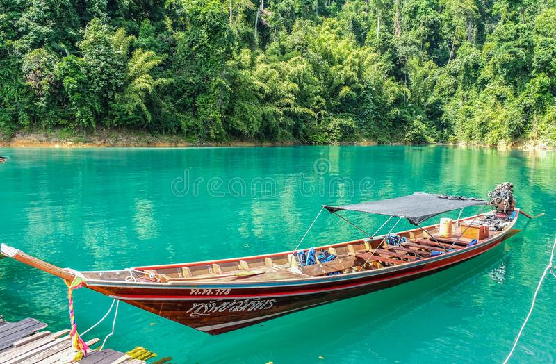 Wooden Thai traditional long-tail boat on a lake with mountains and rain forest in the background during a sunny day at Ratchaprap royalty free stock photo