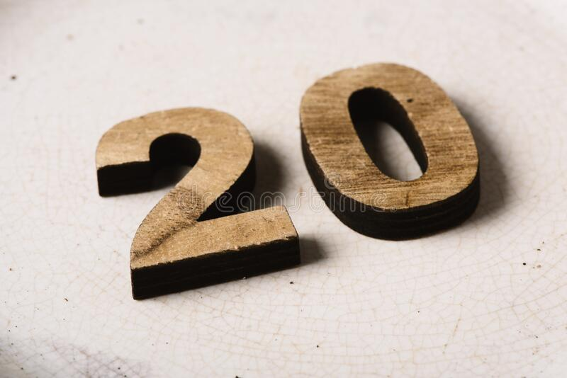 Wooden three-dimensional number 20. Closeup of two wooden three-dimensional numbers forming the number 20 on a cracked white ceramic surface stock image