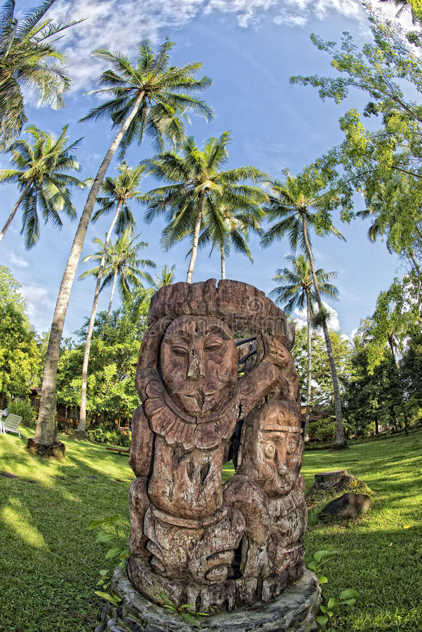 Wooden tiki on tropical paradise beach. With coconut trees stock images