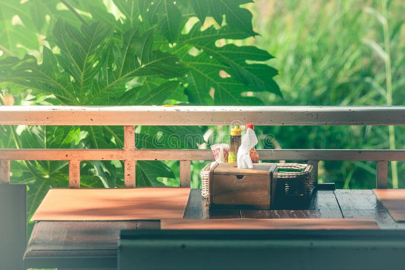 Wooden tissue box and garnish in basket salt, pepper, toothpick, sauce on table with green trees and sunlight background. stock images
