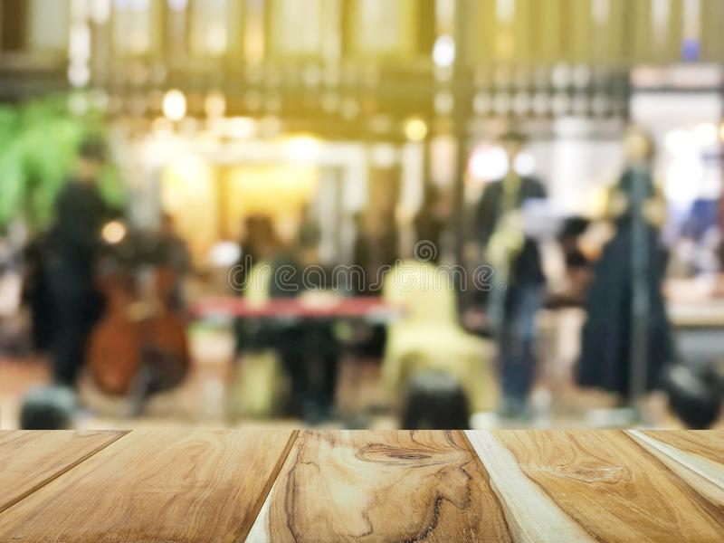 Wooden top table over blurred background of music band in restaurant for display the products. stock photo
