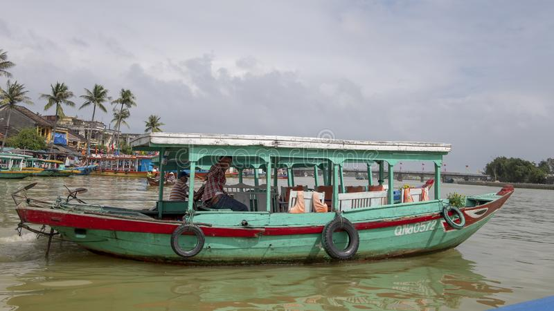 Wooden tour boat, teal color with red trim, on the Thu Bon river in Hoi An, Vietnam. stock photo