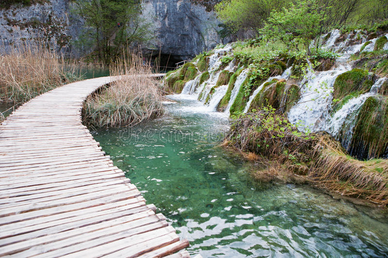 Wooden tourist pathway passing through waterfalls royalty free stock photography