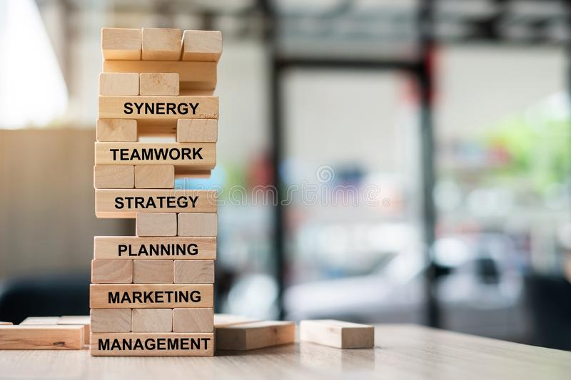 Wooden tower building with text; Synergy, Teamwork, Strategy, Planning, Marketing and Management. Business Concepts royalty free stock photo