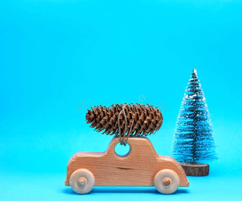Wooden toy car carries on top a pine cone on a blue background. Christmas background royalty free stock photography