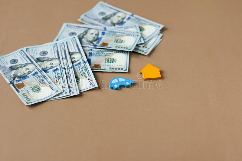 Wooden toy car and house with dollars. On table royalty free stock photo