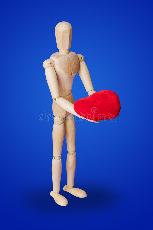 Wooden toy figure with heart on blue stock image