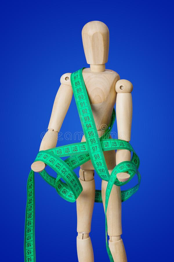 Wooden toy figure with measuring tape on blue stock photos