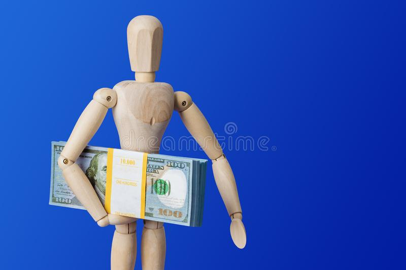 Wooden toy figure with money on blue royalty free stock image