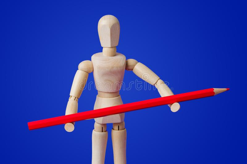 Wooden toy figure with pencil on blue stock image