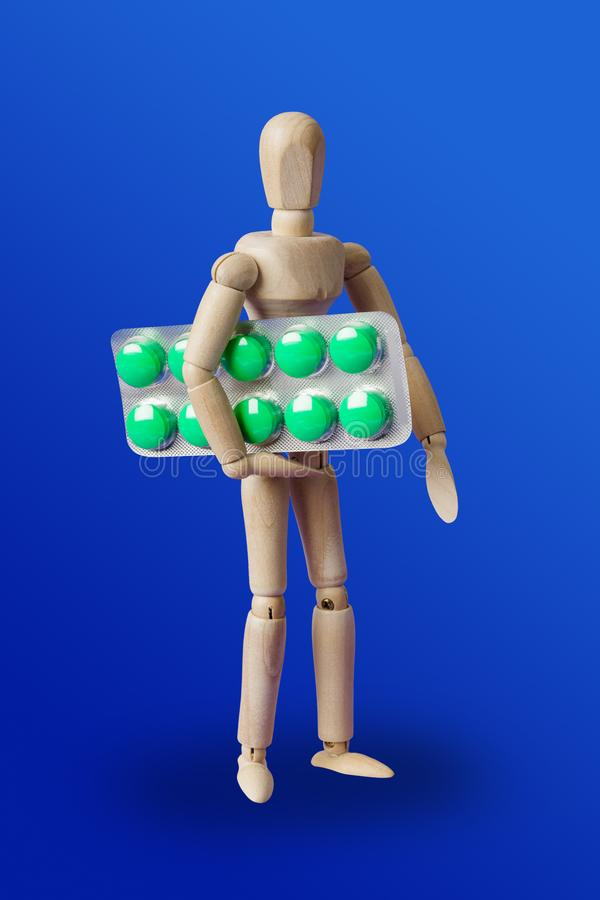 Wooden toy figure with pills on blue royalty free stock photo