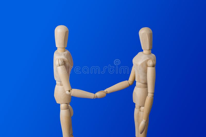 Wooden toy figures handshake on blue royalty free stock photos