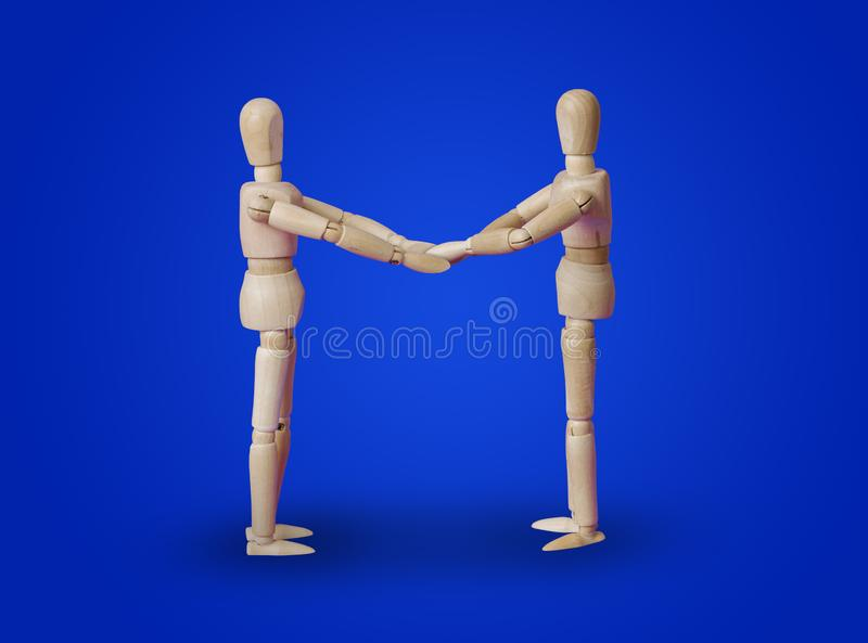 Wooden toy figures handshake on blue royalty free stock images