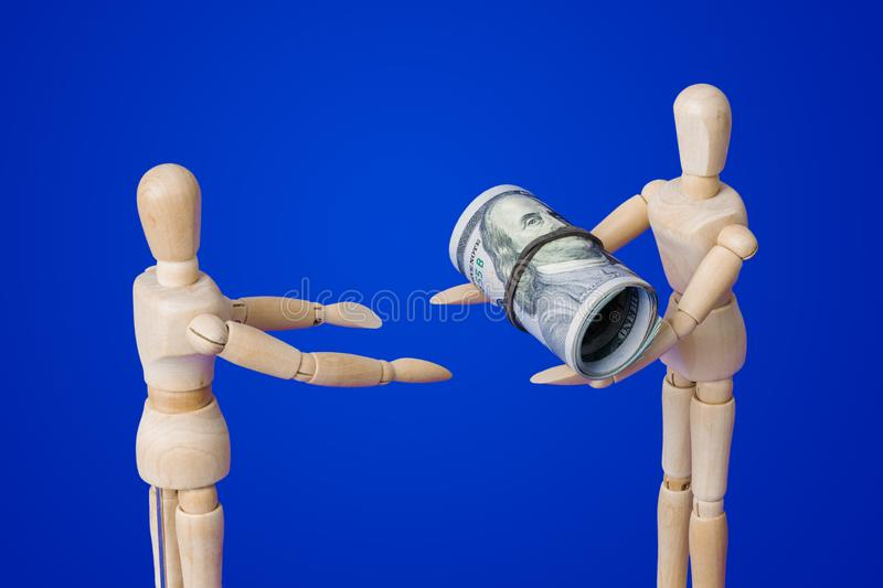 Wooden toy figures with money on blue stock photography