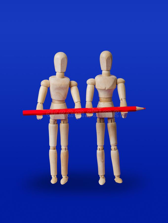 Wooden toy figures with pencil on blue stock photos