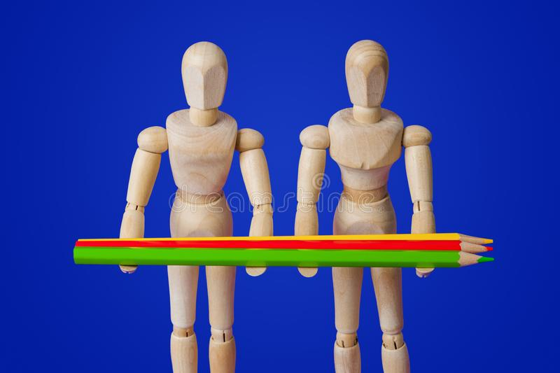 Wooden toy figures with pencils on blue royalty free stock images