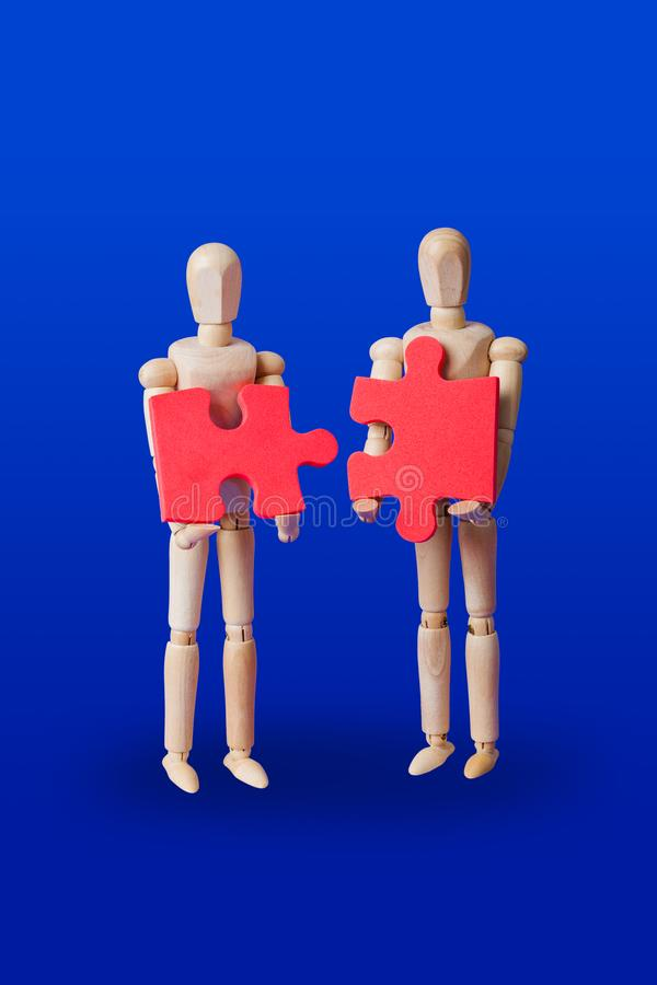 Wooden toy figures with puzzle on blue royalty free stock photo