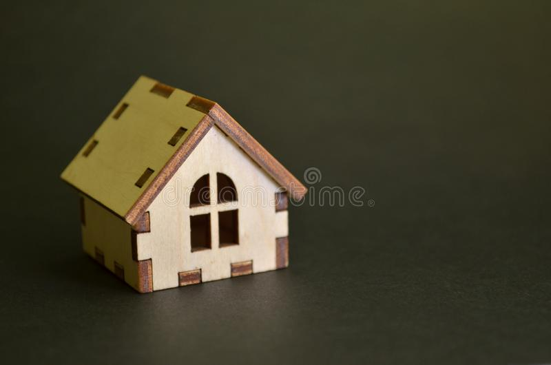 Wooden toy house model on a black background with copyspace. Wooden toy house model on black background with copyspace stock image