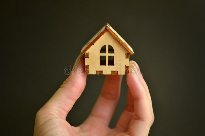 Wooden toy house model in woman hand on black background front view, with a copyspace. Wooden toy house model in woman hand on black background front view, with stock photo