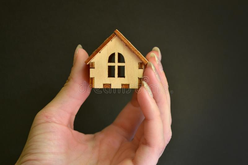 Wooden toy house model in woman hand on black background front view, with space for text. Wooden toy house model in woman hand on black background front view stock photos