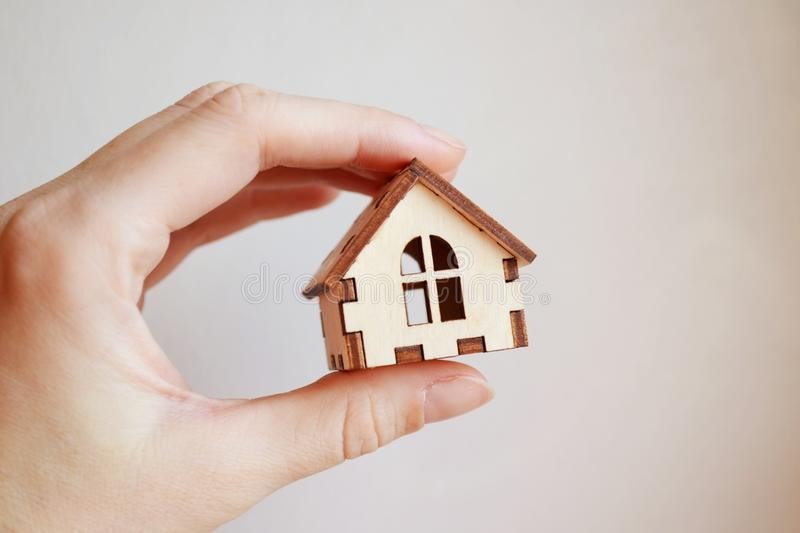 Wooden toy house model in woman`s hand on white background front view royalty free stock images