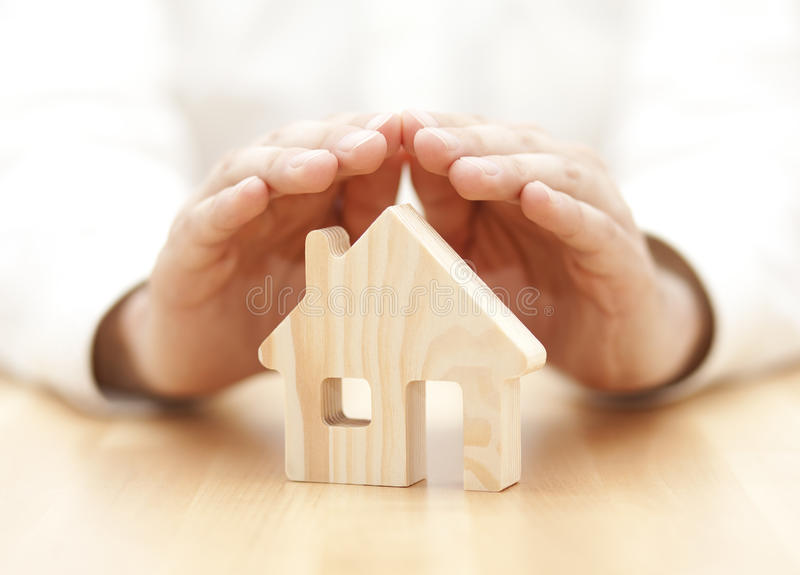Wooden toy house protected by hands. Wooden pine toy house protected by hands stock photo