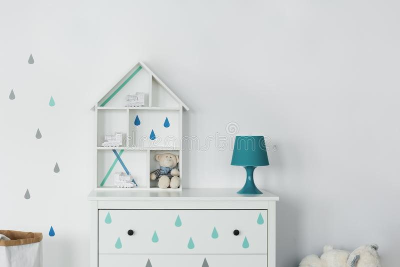 Wooden toy house. On a wardrobe in a baby room stock photos