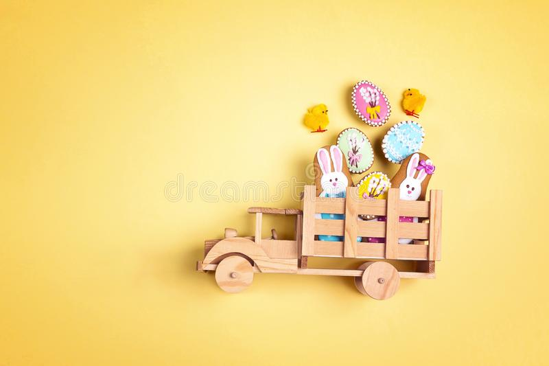 Wooden toy truck with Easter homemade gingerbread cookies  in the back on yellow background. Funny Easter decoration. Gingerbread in shape of easter bunny and royalty free stock photo