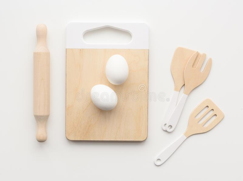 Wooden toys for children. Play kitchen utensils: cutting board, rolling pin and spatulas with raw eggs on white background stock photo